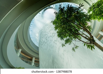 Singapore / Singapore - April 17 2019 : Jewel Changi Airport Rain Vortex. This is the largest indoor waterfall in the world and the centerpiece of Jewel Changi Airport.
