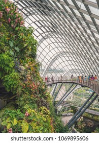 Singapore - April 2, 2018: Gardens by the Bay. Large atrium and botanic garden. People walking on the bridge.