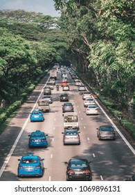 Singapore - April 2, 2018: Rush hour on highway covered with tropic forest in the center of city.