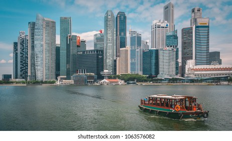 Singapore - April 2, 2018: Skyscrapers in Singapore. Modern architecture cityscape, skyline. Asian style boat passing by.