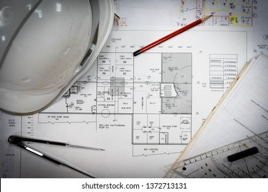 Singapore - April 2019: White safety helmet and drawing tools on naval architects working desk
