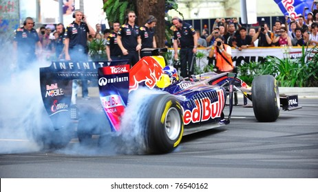 SINGAPORE - APRIL 24: David Coulthard performing burnouts in the Red Bull Racing F1 car RB6 during Red Bull Speed Street Singapore on April 24, 2011 in Singapore.