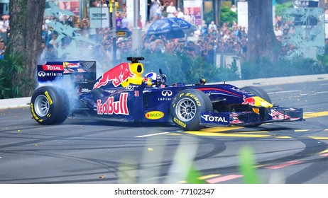 SINGAPORE - APRIL 24: David Coulthard performs donuts in the Red Bull Racing F1 car RB6 during Red Bull Speed Street Singapore on April 24, 2011 in Singapore.