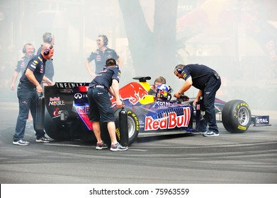 SINGAPORE - APRIL 24: Red Bull Racing pit crews cool the F1 RB6 car after David Coulthard performed donuts during Red Bull Speed Street Singapore on April 24, 2011 in Singapore.
