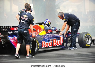 SINGAPORE - APRIL 24: Red Bull Racing pit crews cooling the F1 RB6 car after David Coulthard performed donuts during Red Bull Speed Street Singapore on April 24, 2011 in Singapore.