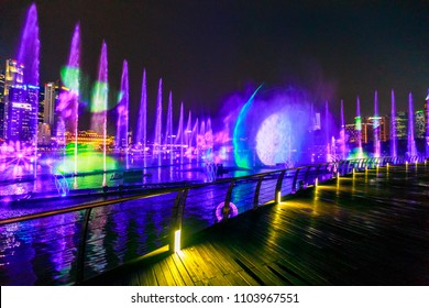 Singapore - April 26, 2018: Spectra: Light and Water Show at Event Plaza along promenade in front of Marina Bay Sands. The show of dancing fountains is one of biggest attractions in Singapore by night
