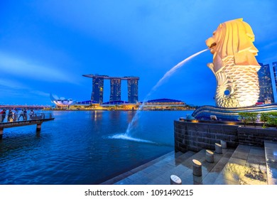 Singapore - April 27, 2018: icon of Singapore Merlion Statue with a lion's head and body of a fish spouting water from the mouth and three towers of Marina Bay Sands with ArtScience Museum. Blue hour.