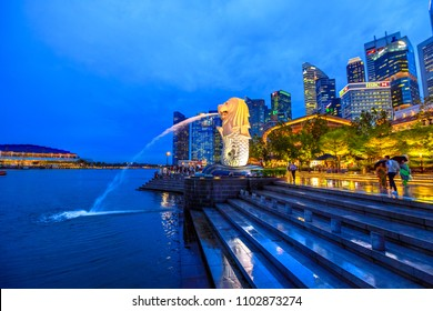 Singapore - April 27, 2018: Merlion Statue in Merlion Park with Central Business District or CBD Buildings illuminated in Marina Bay Harbor and waterfront. Scenic Singapore icon at blue hour.