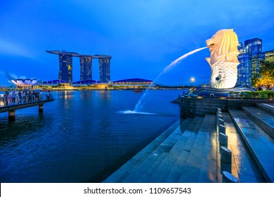 Singapore - April 27, 2018: reflecting statue Singapore Merlion in Marina Bay sea. Merlion has a lion's head and fish body and it's spouting water from its mouth. Marina Bay Sands towers in skyline.