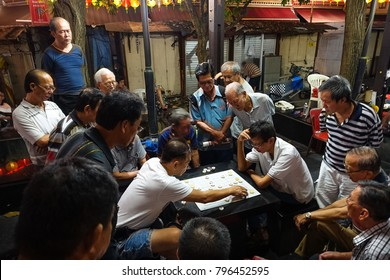Singapore, Singapore - April 28, 2017: Singaporean men gather to watch and play Chinese chess each night in People's Park Complex, Chinatown.