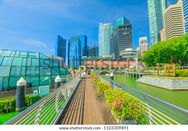 Singapore - April 28, 2018: glass dome of Fullerton Pavilion on Marina Bay Central Business District or CBD Buildings and Clifford Square in Marina Bay promenade Singapore. Sunny day with blue sky.