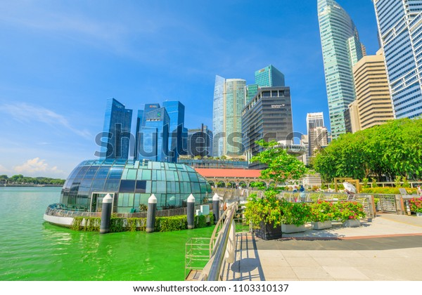 Singapore - April 28, 2018: glass dome of Fullerton Pavilion with Monti restaurant on Marina Bay Central Business District or CBD Buildings in Marina Bay walkway promenade. Daytime with blue sky.
