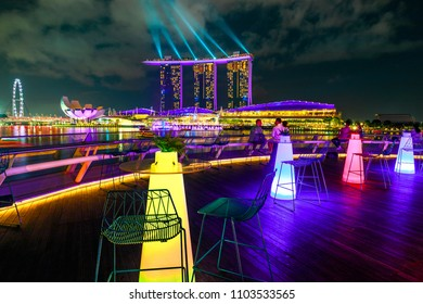 Singapore - April 28, 2018: Marina Bay Sands with colored lights during laser show seen from roof of The Fullerton Pavilion, Italian restaurant Monti At 1-Pavilion in Singapore harbor by night.
