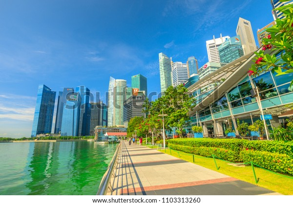 Singapore - April 28, 2018: Marina Bay promenade on a beautiful sunny day with blue sky. Fullerton Pavilion glass dome and Central Business District or CBD Buildings on background.