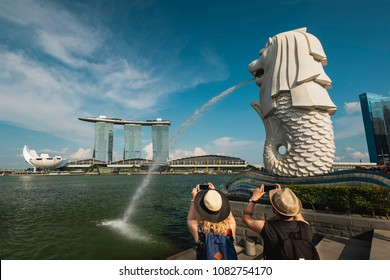 Singapore, Singapore - April 29, 2018: Tourists taking picture of Singapore Merlion and Marina Bay Sands Hotel