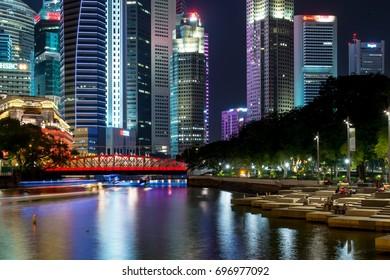 SINGAPORE - AUG 9 2016 :Anderson Bridge on Singapore River with skyscraper  at night, 9 Aug 2016