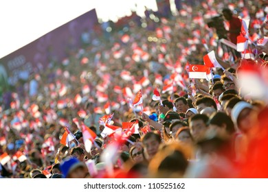 SINGAPORE - AUGUST 09: Audience waving Singapore flags during National Day Parade 2012 on August 09, 2012 in Singapore