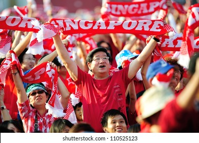 SINGAPORE - AUGUST 09: Enthusiastic audience waving the red Singapore scarves during National Day Parade 2012 on August 09, 2012 in Singapore