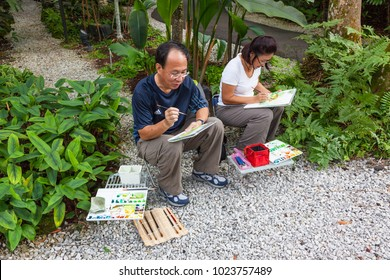 SINGAPORE - AUGUST 16, 2009: Two adult artists, a father and a daughter, painting in watercolors in Singapore Botanic Gardens.