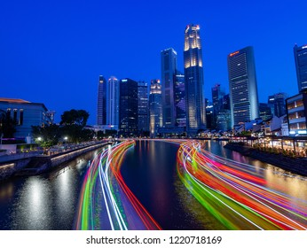 Singapore / Singapore - August, 2018: Singapore skyscrapers and passenger boat light trails at night. Singapore is a sovereign city-state and island country in Southeast Asia.