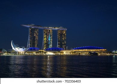 Singapore, Singapore - August 24, 2017: Night view at the Marina Bay district in Singapore with the iconic landmarks of The Helix Bridge, The Marina Bay Sands and The ArtScience Museum.