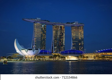 Singapore, Singapore - August 24, 2017: Night view at the Marina Bay district in Singapore with the landmarks of The Helix Bridge, The Marina Bay Sands and The ArtScience Museum.