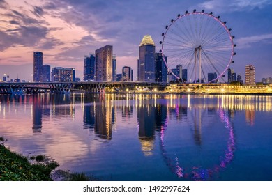 Singapore, Singapore - August 24 2019: The Singapore Flyer big wheel and other buildings seen at sunset from Gardens by the Bay
