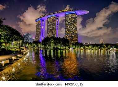 Singapore, Singapore - August 24 2019: The iconic architecture of Marina Bay Sands lights up at night in Singapore's Marine Bay redevelopment zone