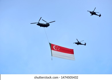 """Singapore - AUGUST 3, 2019: Apache helicopter flying a giant Singapore in the sky as part of Singapore National Day Parade (NDP) rehearsals. The theme for NDP 2019 is """"Our Singapore""""."""