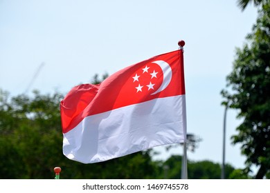 """Singapore - AUGUST 4, 2019: Day time of Singapore flag along the road in public area. To celebration for 54th Singapore National Day. The theme for NDP 2019 is """"Our Singapore""""."""