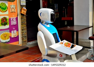 Singapore - August 5 2019: Robot waiter outside Chinese restaurant in Chinatown holding a menu in close up