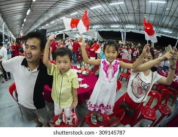 SINGAPORE - AUGUST 8 : A young family sing one of the national day song and wave mini national flags with pride and joy at Pasir Ris - Punggol SG50 National Day dinner event on Aug 8, 2015, Singapore