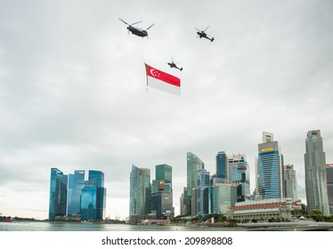 Singapore - August 9, 2014: Singapore National Day helicopter hanging Singapore flag flying over the city