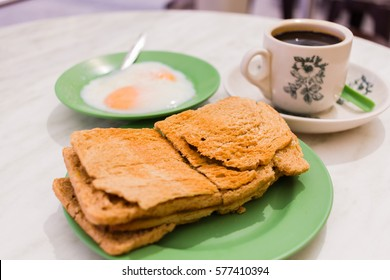 Singapore Breakfast called Kaya Toast, Coffee bread and Half-boiled eggs, Chinese coffee in vintage mug and bread toast with a local jam made from eggs, sugar and coconut milk The cup is generic print