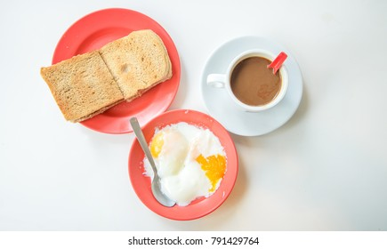 Singapore Breakfast called Kaya toast, half boiled eggs,and hot black tea coffee. Kaya toast is toasted bread filled with butter and kaya, a jam made from eggs, sugar, coconut milk and pandan leaves.