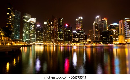Singapore business district in the night time with water reflections.