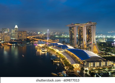 Singapore business district skyline in night at Marina Bay, Singapore. Singapore flyer and Marina bay sands hotel in night at Singapore
