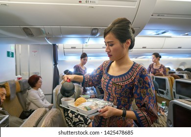 SINGAPORE - CIRCA APRIL, 2019:  flight attendant serve food and drinks to passengers on board of Singapore Airlines Airbus A350.