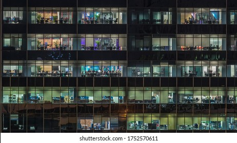 SINGAPORE - CIRCA JAN 2020: Modern office building with big windows at night view close up view, in windows glowing light shines and some people inside, Singapore