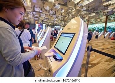 SINGAPORE - CIRCA JANUARY, 2020: a traveller at the self check-in kiosk at Terminal 3, Singapore Changi Airport. Changi Airport is a major civilian airport that serves Singapore.