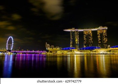 SINGAPORE - CIRCA MARCH 17, 2017 : Singapore in the night. Singapore central business district skyline, pink, yellow, and blue reflection with night skyline from marina bay.