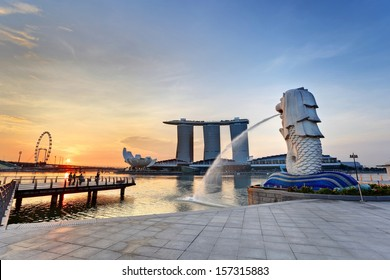SINGAPORE CITY, SINGAPORE: APRIL 13,2013: Sunrise at Merlion and Singapore city skyline with Singapore Flyer.