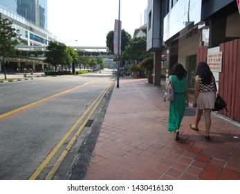 SINGAPORE CITY / SINGAPORE - AUGUST 08, 2012: Asian Singaporean Ladies Walking Together