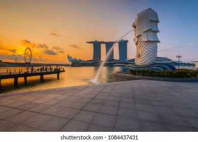 Singapore City - Jul 28, 2016: Sunrise over Merlion and Singapore city skyline with Singapore Flyer at Marina Bay Waterfront.
