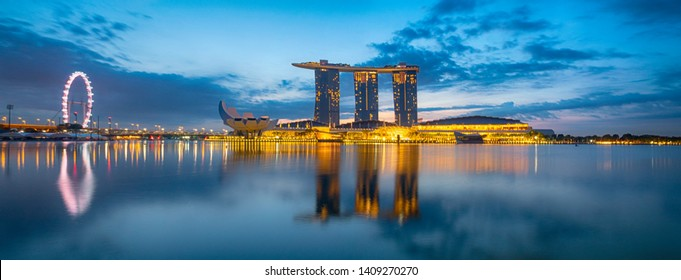 SINGAPORE CITY, SINGAPORE: OCT 29, 2017: Vibrant panorama background of Singapore city skyline at business modern downtown building area cloud and light on sky and reflection the architecture on water