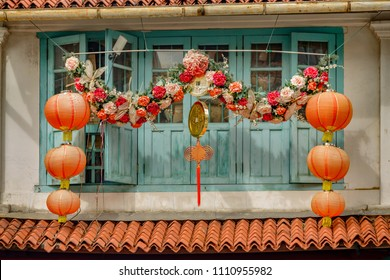 SINGAPORE CITY, SINGAPORE - OCTOBER 08, 2016: Colourful decorations outside wooden houses with shutters and windows in the Little India, district of Singapore.