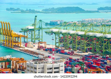 Singapore commercial port aerial view, freight cranes and containers at pier, islands and ships in background