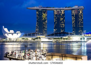 SINGAPORE - DECEMBER 15 2013: People gather to watch the Marina Bay Sands Resort Hotel in Singapore displaying a light show at night.