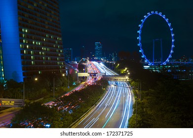Singapore, Singapore - December, 21 : Light trails on the highway in Singapore pass the Singapore Flyer and Marina Bay Sands taken on December 21, 2013