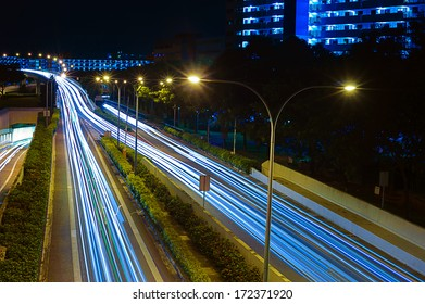 Singapore, Singapore - December, 21: Light trails on Singapore roads with high rise buildings taken at night on December 21, 2013